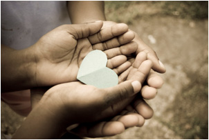 love; beautiful hands of children holding green heart shape
